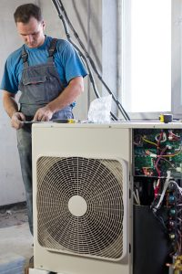 Technician installing a ductless air conditioner in an apartment